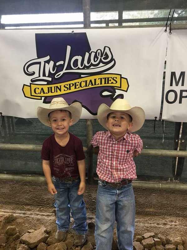 Silver Spurs Rodeo Club - Two young cowboys standing in front of InLaws Cajun banner